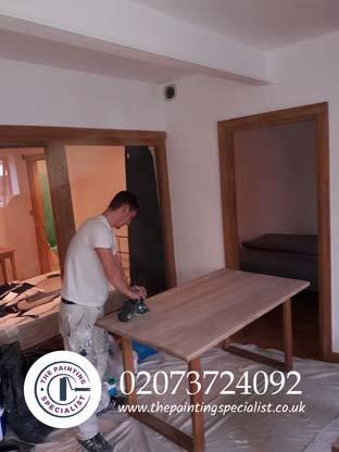 Sanding down a table on a job